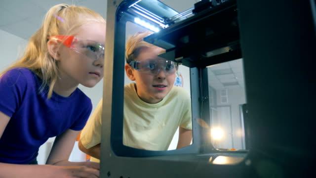 teenager und mädchen beobachten einen funktionierenden technologischen mechanismus - druck physikbegriff stock-videos und b-roll-filmmaterial