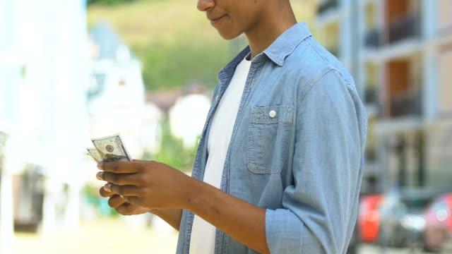 teen pojke räkna pengar överväger inköp för första inkomster, fickutgifter - stavning bildbanksvideor och videomaterial från bakom kulisserna
