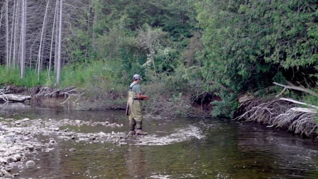 A teen boy fly fishing on a small trout stream