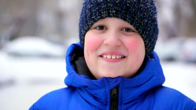 Teen Boy In A Blue Down Jacket Laughing Winter Falling Snow Video