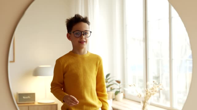 teen boy is choosing new eyeglasses in front of a mirror - optometrist stock videos and b-roll footage