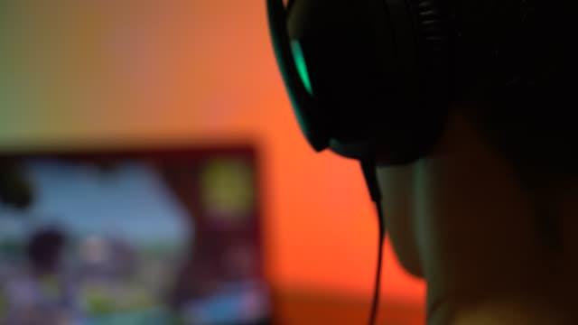 十代の少年がゲームを果たしています。 - ゲーム ヘッドフォン点の映像素材/bロール