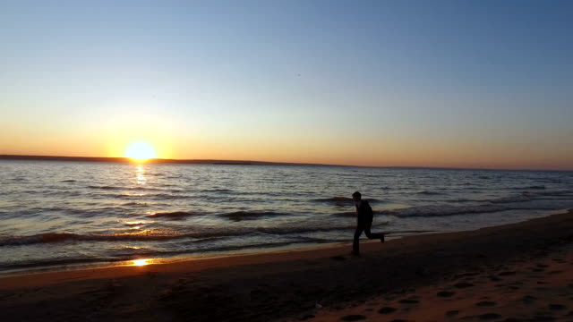 Teen boy runs along the shore of a large lake. It running along the water's edge. video
