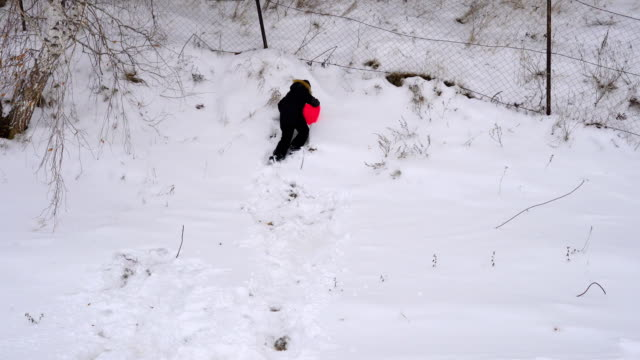 Teen boy trying to ride on the hillside. Winter fun for children in the park. A cloudy winter day. video
