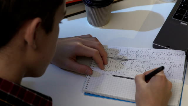 Teen boy trying to solve difficult equation in notebook, preparing for math exam video