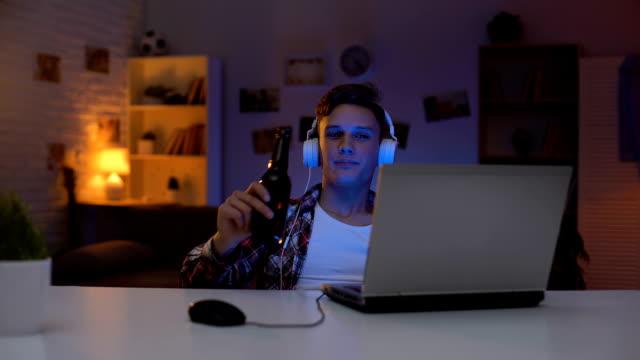 stockvideo's en b-roll-footage met tiener jongen kijken naar film op laptop, bier drinken, eten snacks, tijdverlies - kids online abuse
