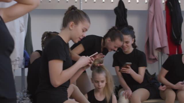 teen cheerleading team redo i omklädningsrummet - gympingdräkt bildbanksvideor och videomaterial från bakom kulisserna