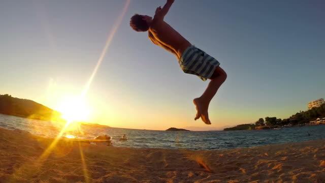 vídeos de stock, filmes e b-roll de adolescentes fazendo ginástica de flip na praia ao pôr do sol em câmera lenta - pessoas bonitas