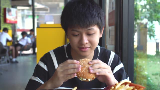 Teen eating hamburger.