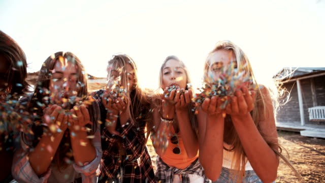Teen friends blowing colorful confetti on sunny summer evening