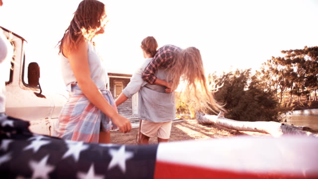 Teen friends carrying an American flag outside video