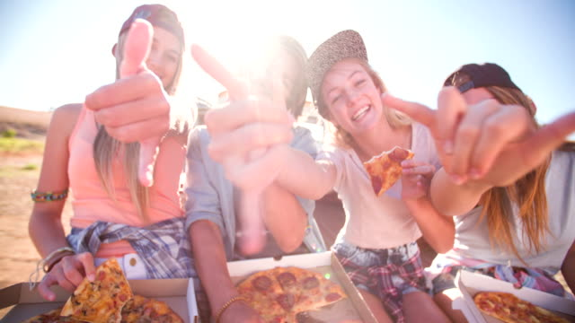 Teen friends eating pizza together outdoors with sun flare video