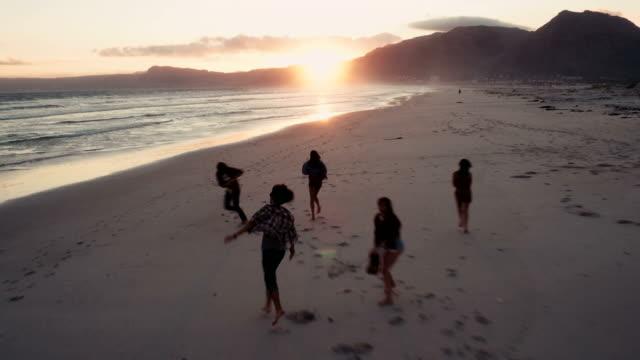 Giovani amici godendo di una passeggiata sulla spiaggia al tramonto - video
