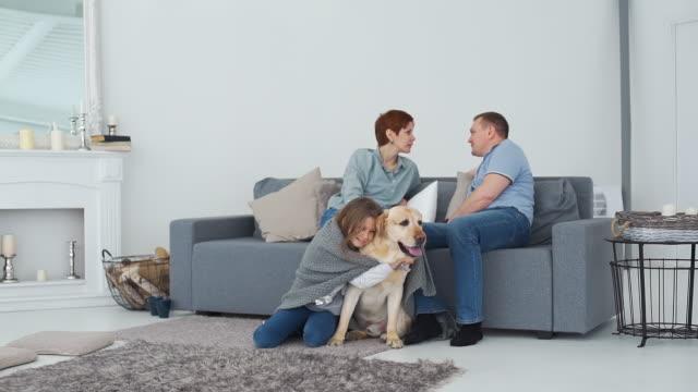 Teen Girl Embracing Dog near Parents at Home