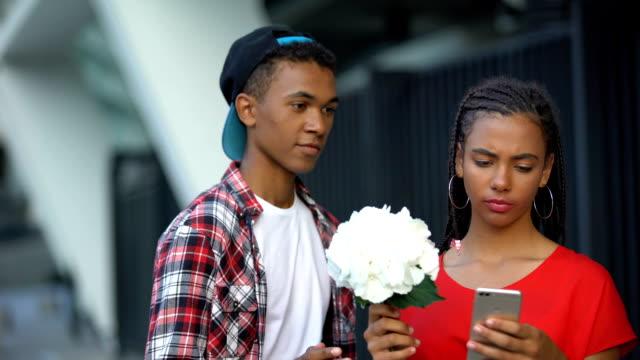 stockvideo's en b-roll-footage met tiener meisje negeert bloemen van jongen, voorkeur aan sociale netwerken, digitale natie - kids online abuse