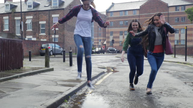 teen girl jumping into a puddle while its raining - teenagers stock videos and b-roll footage