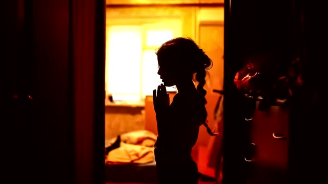 teen girl praying silhouette in corridor brown evening religion video