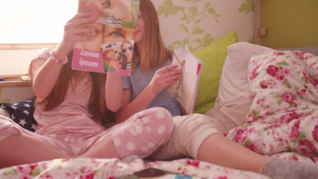 vídeos y material grabado en eventos de stock de teen chica mostrando su amigo un nuevo la revista de moda - moda playera
