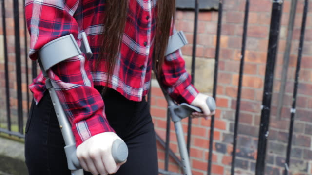 Teen Girl Struggles on Her Crutches A young teen girl in crutches walking home by herself, hopping along crutch stock videos & royalty-free footage