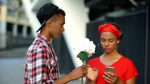 stockvideo's en b-roll-footage met tiener meisje onbewust nemen bloemen van jongen, digitale natie verslaafd aan gadget - kids online abuse