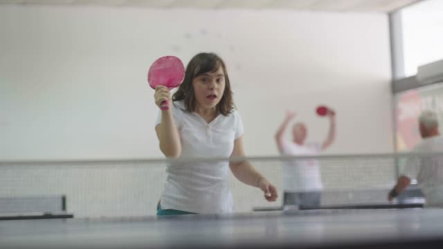 vídeos de stock e filmes b-roll de teen girl with down syndrome playing table tennis - pessoas com deficiência