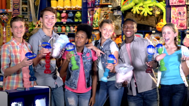 Teen girl with malformed arm, friends at arcade