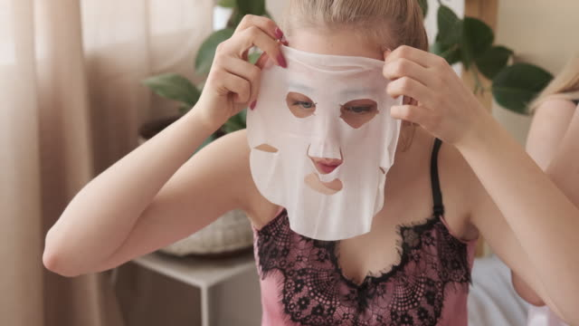 Teen girls applying moisturizing facial tissue mask Beautiful teen girl friends applying a moisturizing facial tissue mask while getting ready for party sister stock videos & royalty-free footage
