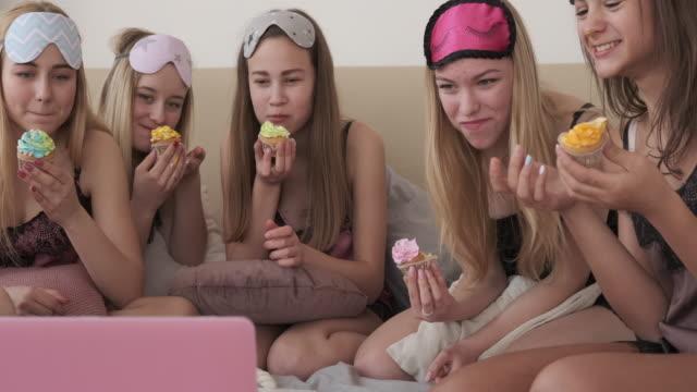 パジャマパーティー中にカップケーキを食べ、映画を見て十代の女の子 - カップケーキ点の映像素材/bロール