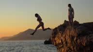 istock Teen girls having fun at the Adriatic coast, jumping from a rock into the sea at sunset and swimming back to the coast 1285710471