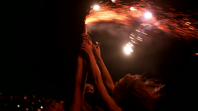 Teen girls holding sparkling fireworks at night at the harbor video
