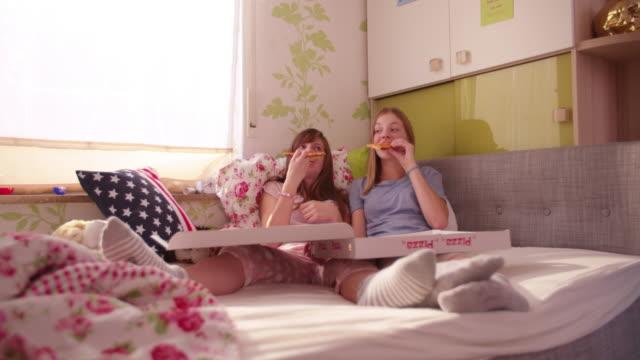 vidéos et rushes de teen fille souriante dans une chambre à une pizza géante - fête de naissance