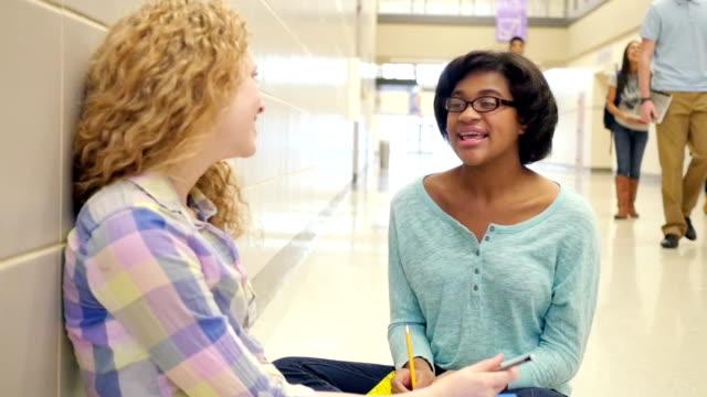 Teen Mädchen Sitzen im Flur der high school und reden nach dem Kurs – Video