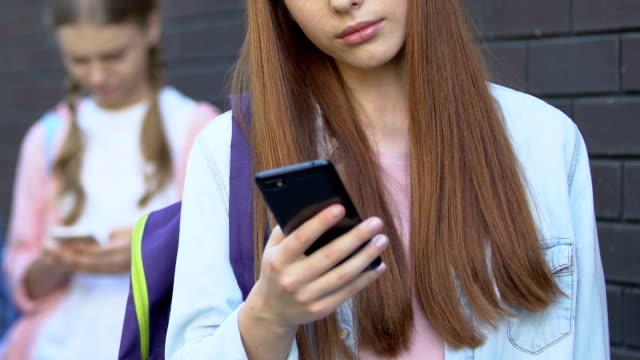 stockvideo's en b-roll-footage met tiener meisjes met behulp van mobiele telefoons, chatten in sociaal netwerk, internetverslaving - kids online abuse