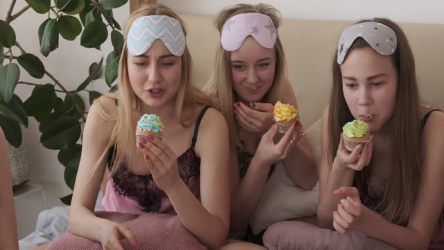 Teen girls watching movie and eating cupcake during pajama party