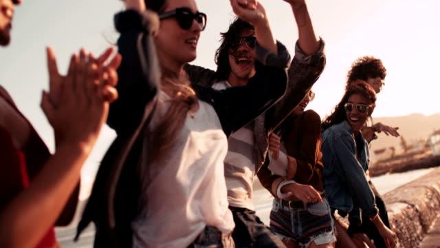 Giovani hipster gli amici ballare sul molo al tramonto - video