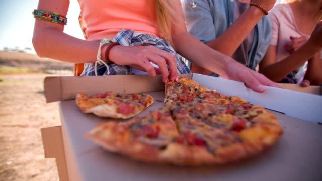teen hält ein stück pizza mit freunden im hintergrund - teenage friends sharing food stock-videos und b-roll-filmmaterial