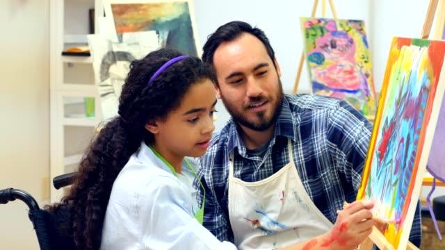 Teen in wheel chair paints with teacher during art class