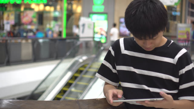 Teen playing a tablet in a mall.
