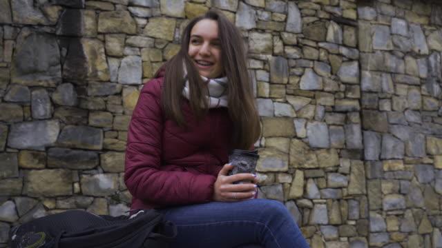 tonåring anda. vacker tonårs flicka på hennes smartphone efter en lång skoldag.. - endast en tonårsflicka bildbanksvideor och videomaterial från bakom kulisserna