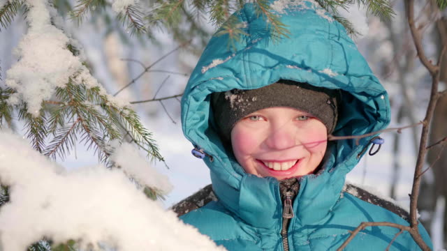 Teen walks in winter Park. Resets the snow from the trees. Walks in the fresh air. A healthy lifestyle video