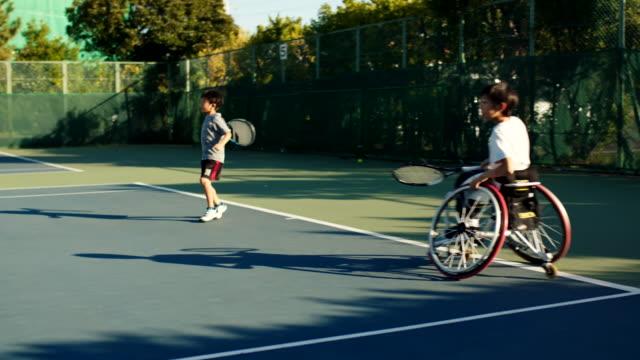 ダブルステニスをプレイするslo mo 10代の適応テニス選手 - disabilitycollection点の映像素材/bロール