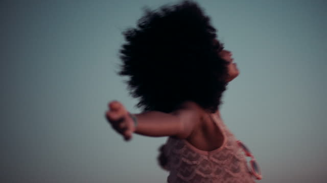 Teenage afro girl enjoying sunset at beach video