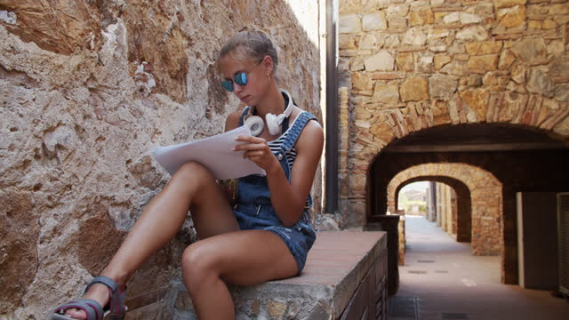 Teenage art student sketching in an Italian town Teenage art student sitting in Italian town and sketching the beautiful narrow street. Sunny summer day. BMPCC4K italian architecture stock videos & royalty-free footage