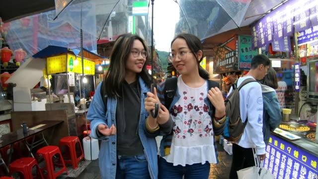 genç asyalı kızlar taipei bir alışveriş pazarında yürüyüş - pazarcı stok videoları ve detay görüntü çekimi