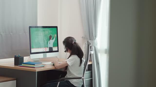 en tonårig asiatisk kvinna studerade matematik med lärare online via dator i sovrummet hemma under hemundervisning medan skolan var stängd på grund av covid-19 utbrott. - digital reading child bildbanksvideor och videomaterial från bakom kulisserna