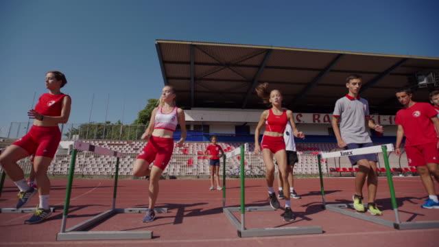 vídeos y material grabado en eventos de stock de atletas adolescentes hurdling en el entrenamiento - valla artículos deportivos