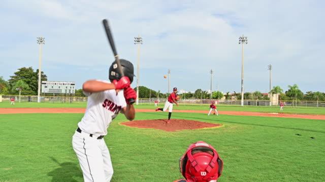 teenage baseball player at bat pops up for the out - sprzęt sportowy filmów i materiałów b-roll
