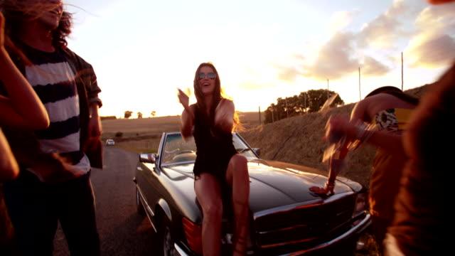 Teenage boho friends sitting on a convertible hood at sunset video