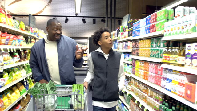 Teenage boy and father shopping in supermarket A father and son shopping together in a supermarket buying groceries pushing a shopping cart, walking down an aisle. The son is 14 years old, mixed race African-American and Hispanic. His father is a mature man in his 40s. snack aisle stock videos & royalty-free footage