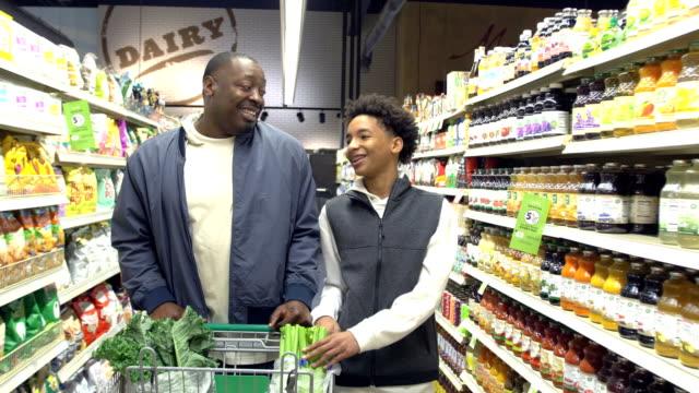 vídeos y material grabado en eventos de stock de adolescente niño y padre de compras en el supermercado - snack aisle
